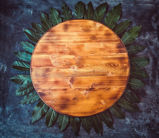 Round empty wooden cutting board with bay leaf around on a dark gray textured background. top view. copy space