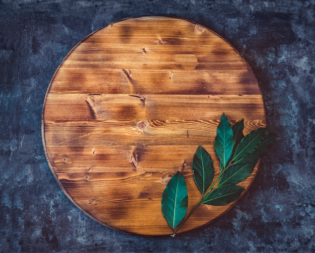 Round empty wooden cutting board with bay leaf branch on a dark gray textured background. top view. copy space