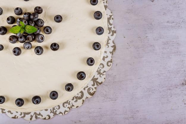 Круглый праздничный торт со свежей черникой и мятой на вершине