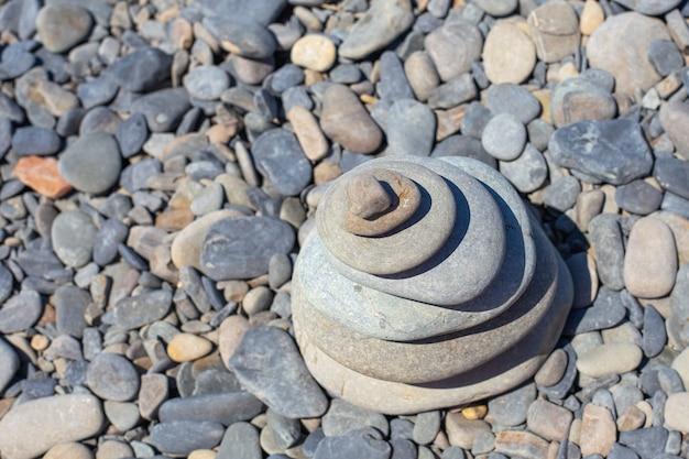 Круглые плоские камни, сложенные в пирамиду на галечном морском пляже, вид сверху. скопируйте пространство. концепция путешествий и туризма.