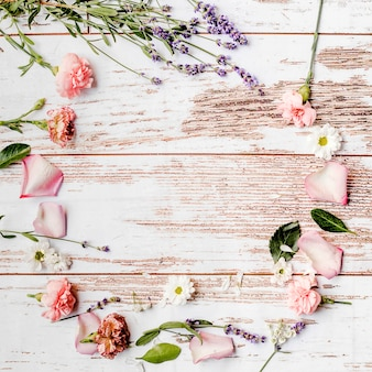 Round floral frame made over wooden background