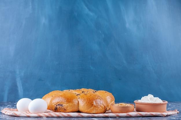 둥근 꽃 모양의 빵, 계란, 밀가루 및 곡물은 파란색 테이블에 티 타월에 있습니다.