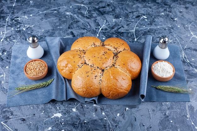 Pane tondo a forma di fiore, sale, farina e grano su pezzi di tessuto su blu.