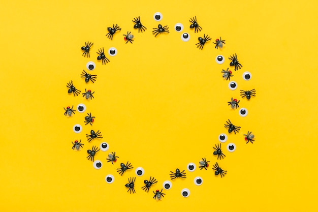 Round frame of black spiders and flies, googly eyes. top view flat lay happy halloween creative concept holiday card mock up.