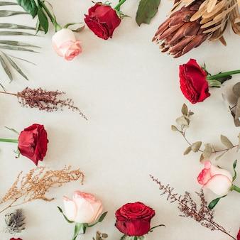 Круглая рамка-бордюр из розовых, красных роз, протея, тропических пальмовых листьев, эвкалипта на бежевом
