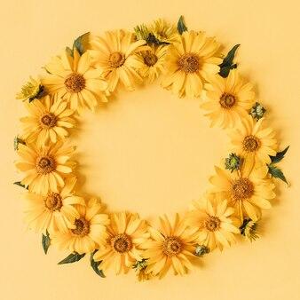 노란색 표면에 노란색 데이지 꽃의 라운드 프레임 테두리
