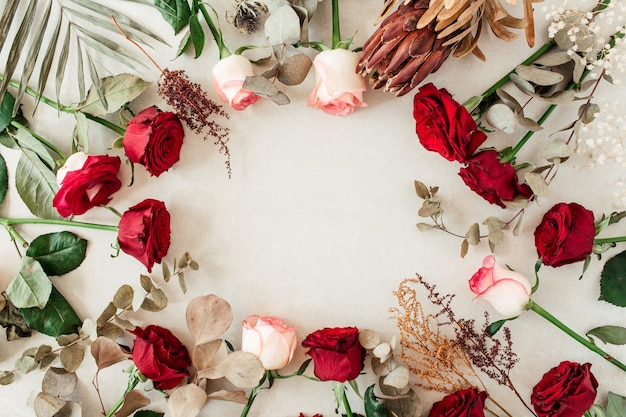 Round frame border of pink, red rose flowers, protea, tropical palm leaf, eucalyptus on beige