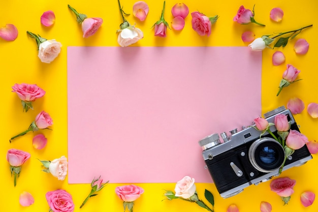 Round frame floral pattern  made of pink and beige roses, green leaves and film camera on yellow background.valentine's day background.