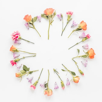 Round frame from different flowers on table