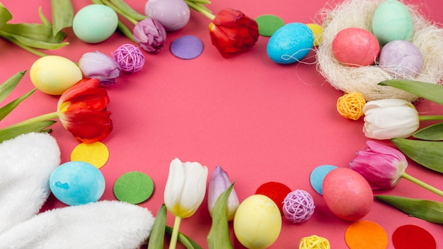 Round frame from easter eggs and tulips on red table