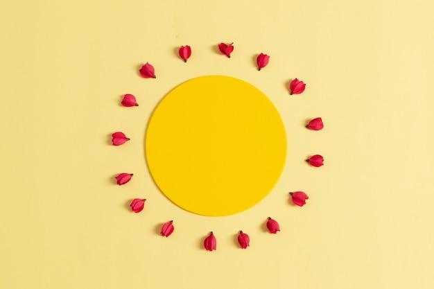 Круглая рамка из красных цветов в виде солнца на желтом фоне. flat lay
