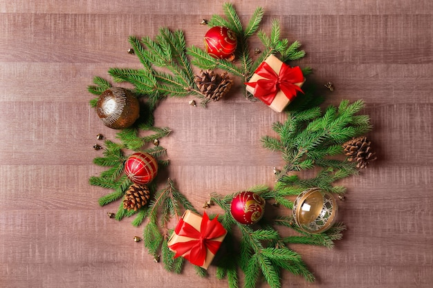 Round frame made of fir tree branches and christmas decor on wooden background