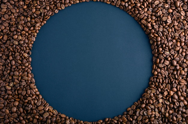 Round frame made from coffee beans on black background. gorizontal arrangement. top view. copy space for text.