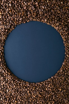 Round frame made from coffee beans on black background. vertical arrangement. top view. copy space for text.
