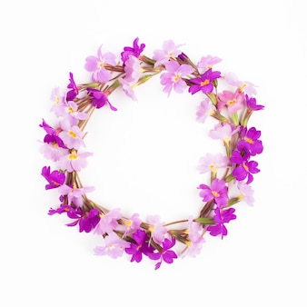 Round frame made of  lilac and purple  flowers on white background flat lay top view