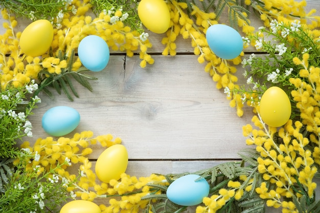 미모사 가지와 나무 판에 부활절 달걀으로 만든 둥근 프레임