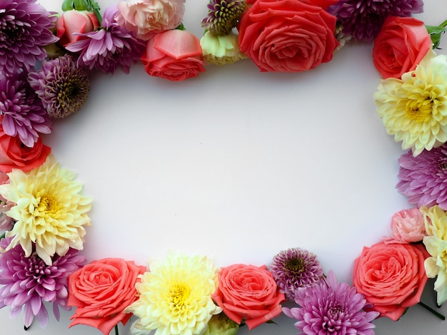 Round frame made of pink and beige roses, green leaves, branches