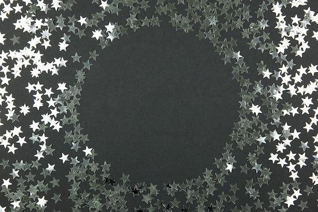 Макет круглой рамки с праздничным праздничным блеском конфетти на темном фоне