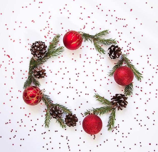 クリスマスツリーの丸いフレームは、白い背景のコピースペースに赤と金の装飾を分岐します