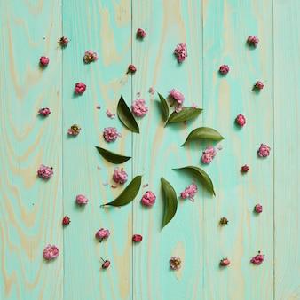 花と葉の丸いフレームは、木製の青い背景に平らに横たわっていた