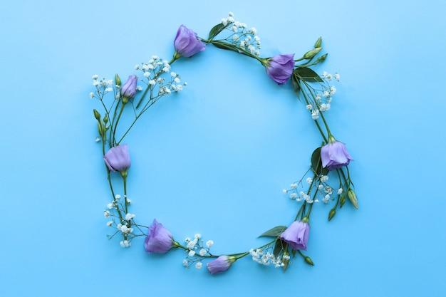 青いテーブルの上に花の丸いフレーム、デザインおめでとう、トップビューの基礎