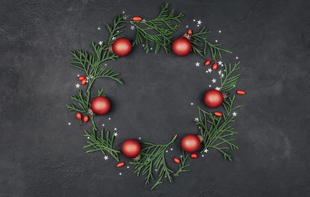 Круглая рамка из зеленых веток и красных новогодних шаров на черном