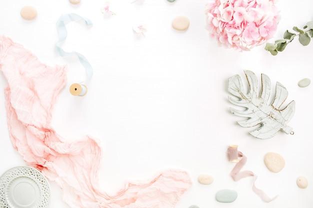 あじさいの花の花束、ユーカリの枝、パステルピンクの毛布、白い表面のモンスターの葉のプレートの丸いフレーム