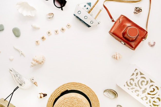밀짚 모자, 레트로 카메라, 새 조각, 장난감 보트, 흰색 표면에 조개와 함께 여행 구성의 라운드 프레임