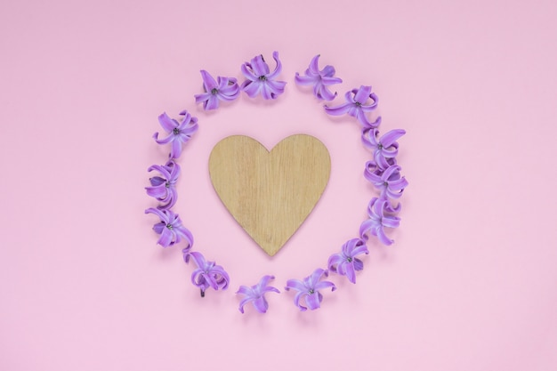 Round frame of pastel purple hyecinth flowers and wooden heart on gradient pink. floral wreath. layout for holidays greeting of mothers day, birthday, wedding or other happy event