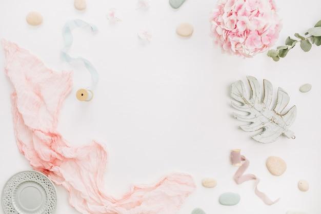 アジサイの花の花束、ユーカリの枝、パステルピンクの毛布、白い表面にモンスターの葉のプレートのテキストのためのモックアップスペースと丸いフレーム