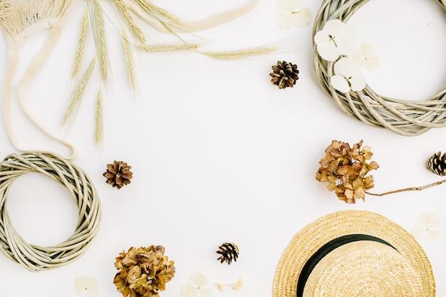 花輪フレーム、ひも悪い、ライ麦の耳、コーン、乾燥した葉、白い背景の上の麦わら帽子のテキストのモックアップスペースと丸いフレーム。フラットレイ、トップビュー秋秋モックアップコンセプト。