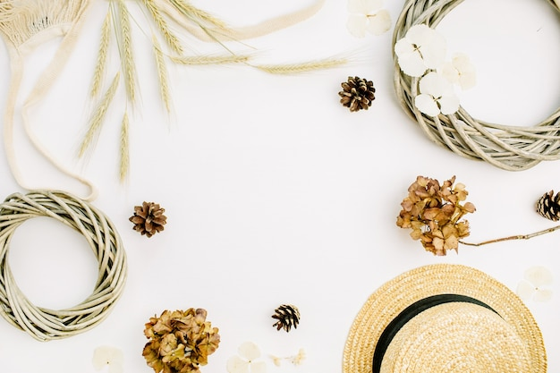 Round frame with mockup space for text of wreath frame, string bad, rye ears, cones, dry leaves, straw hat on white background. flat lay, top view fall autumn mock up concept.