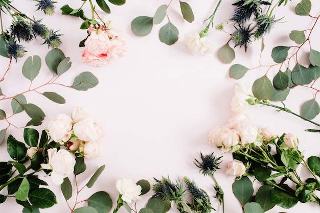 Round frame wreath made of beige rose flowers, eringium flower, eucalyptus branches and leaves on pale pastel pink