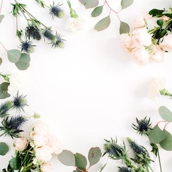 ベージュのバラの花、エリンギウムの花、白のユーカリの枝で作られたラウンドフレームリース