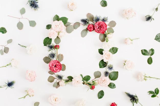 赤とベージュのバラの花のつぼみ、ユーカリの枝と葉で作られた丸いフレームの花輪は白で隔離されます