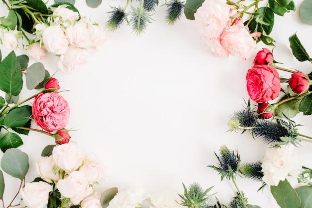 赤とベージュのバラの花、エリンギウムの花、ユーカリの枝と白の葉で作られたラウンドフレームリース