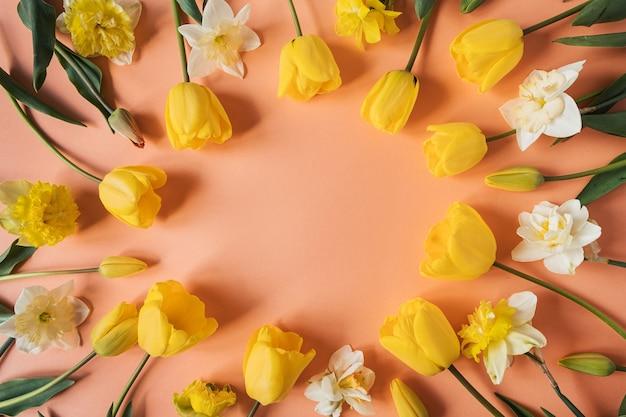 Венок в круглой рамке из желтого нарцисса и цветов тюльпана на розовом персике