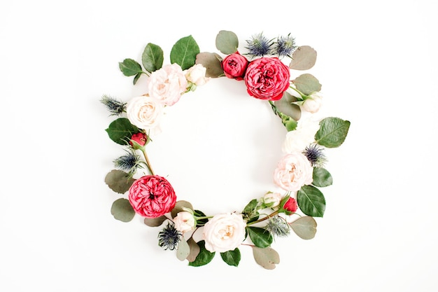 Round frame wreath made of red and beige rose flower buds, eucalyptus branches and leaves isolated on white