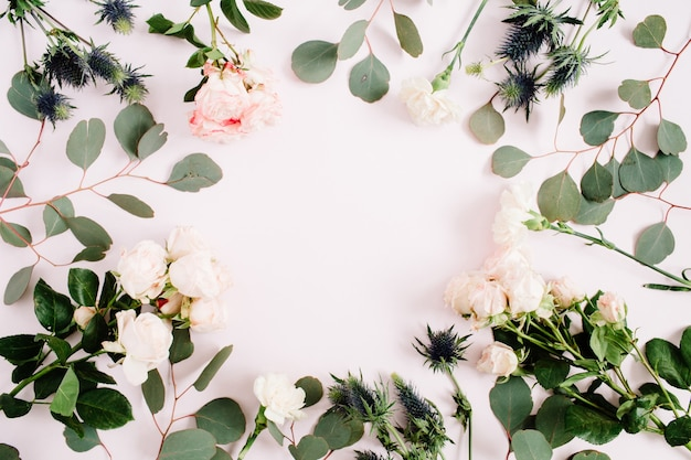 Round frame wreath made of rose flowers, eringium flower, eucalyptus branches on pale pastel pink