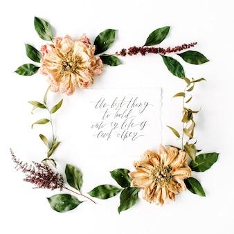 書道のスタイルで書かれたインスピレーションの引用、ベージュの乾燥した牡丹の花、枝と葉が白で隔離されたラウンドフレームの花輪パターン