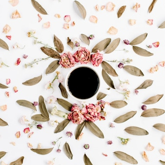 Round frame wreath pattern with roses, coffee cup, pink flower buds, branches and dried leaves on white surface