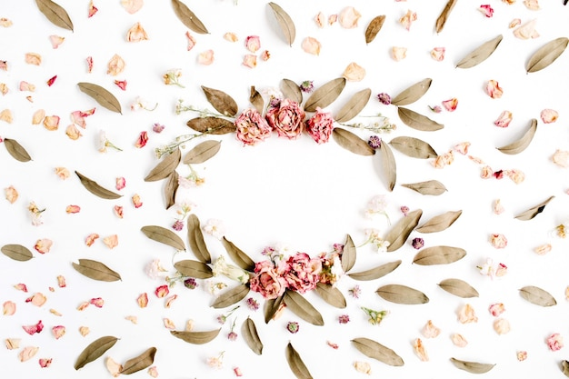 Round frame wreath pattern with roses, pink flower buds, branches and dried leaves isolated on white surface