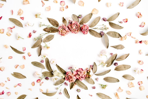 Round frame wreath pattern with roses, pink flower buds, branches and dried leaves on white surface