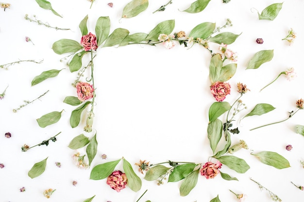 Round frame wreath pattern with roses, pink flower buds, branches and leaves on white surface