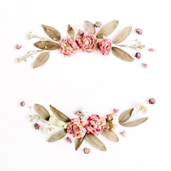 Round frame wreath with roses, pink flower buds, branches and dried leaves isolated on white surface