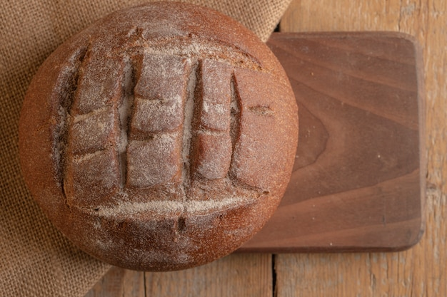 A round french rye bread on a wooden board.