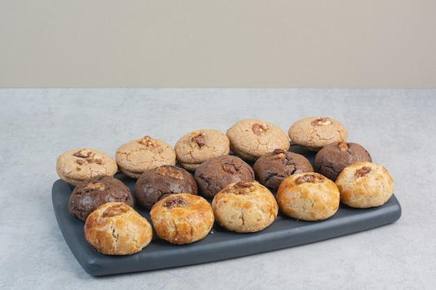 Круглое свежее вкусное печенье на темной тарелке.