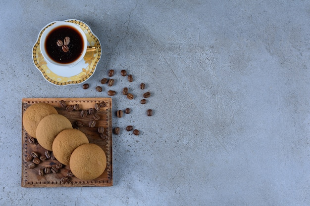 Round fresh sweet cookies with coffee beans and a glass cup of tea.