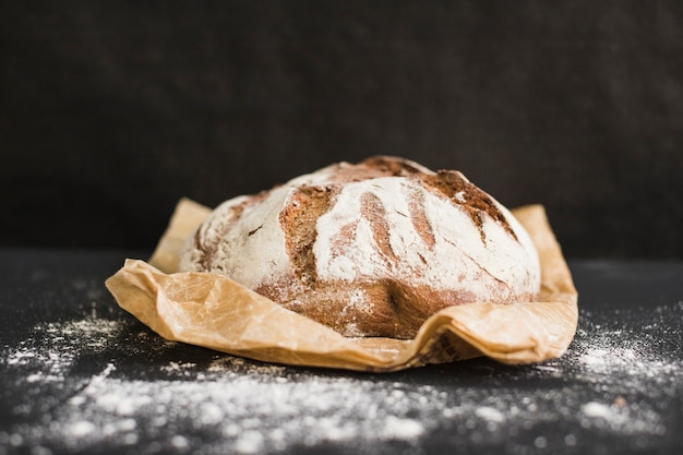 Round freshly baked rustic rye round bread on brown paper against black background