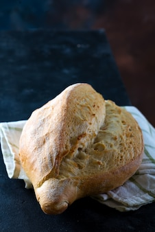 Round freshly baked rustic rye round bread with wheat ears and napkin on dark